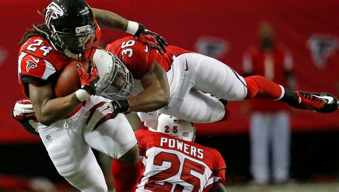 Atlanta Falcons running back Devonta Freeman (24) is hit by Arizona Cardinals strong safety Deone Bucannon (36) during the first half on Sunday, Nov. 30, 2014, in Atlanta.