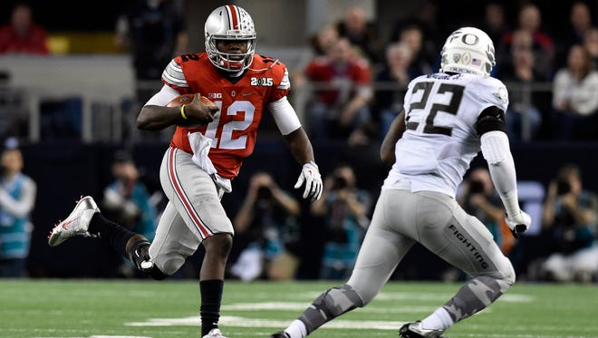 Ohio State Buckeyes quarterback Cardale Jones (12) runs the ball against Oregon Ducks linebacker Derrick Malone (22) during the third quarter in the 2015 CFP National Championship Game at AT&T Stadium.