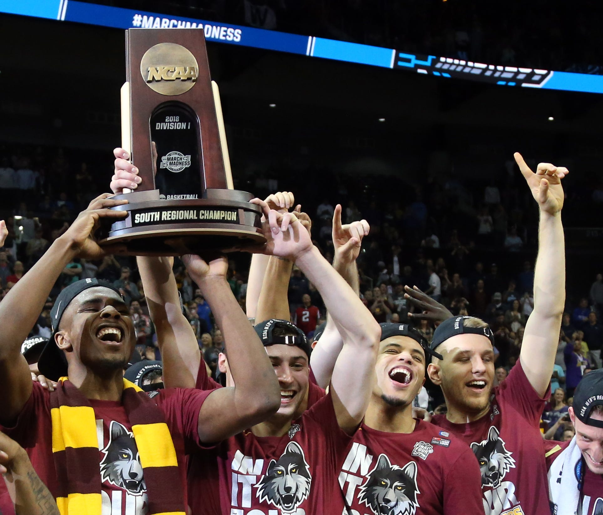 The Loyola Ramblers celebrate with the trophy representing the South Region champ.