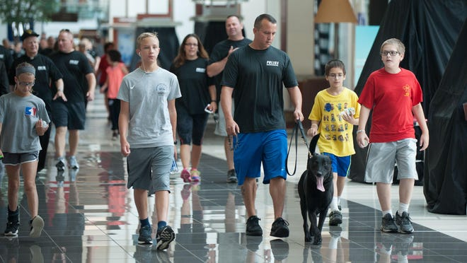 (From left) Jaden Kelly, 10, Jordan Kelly, 14, Sergeant Joe Kelly, Sean Kunz, 10, and Christopher Kunz, 12, all of Cherry Hill, participate in a walk through the Cherry Hill Mall Tuesday morning, June 23, 2015, for the victims of the recent Charleston church attack.