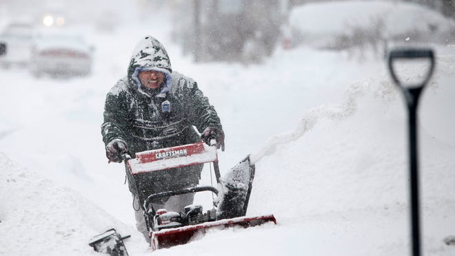 Robert Santiago helps snow blow the driveways of his neighbors on Avenue D in the city during Monday's snowstorm.