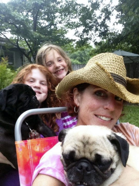 Kelly Meisenhelter and her daughters, Addison and Gillian, are pictured with their pugs, Artie and Binka. Binka, the buff-colored pug, was hit by a car on May 7, and needed surgery to amputate her leg. Meisenhelter said people donated more than 1,000 in 24 hours through a GoFundMe page she set up to pay for Binka's medical expenses, which she didn't have the money to pay for.