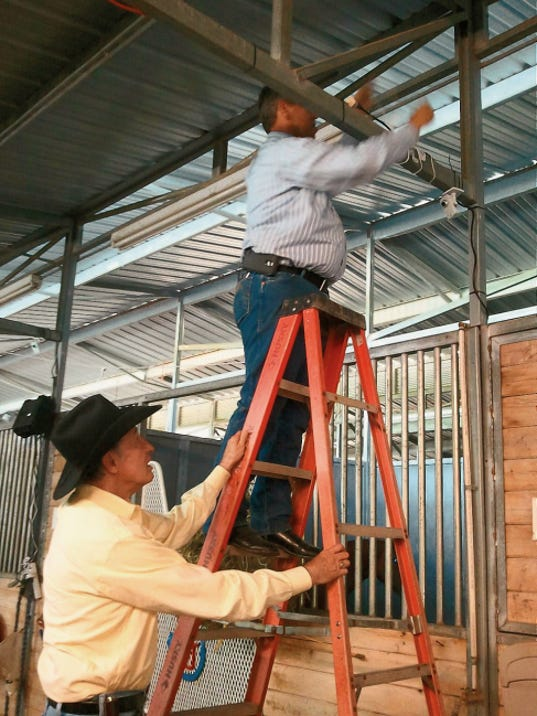 Director of Security Ron Burnum and Dennis Monroe, Integrity Laison Officer for Ruidoso Downs Race Track installing cameras in the barn area.
