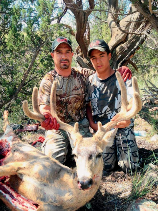 Courtesy Photo   Michael Aguirre Junior, left, poses with his eight-point buck and his son Michael Aguirre III.