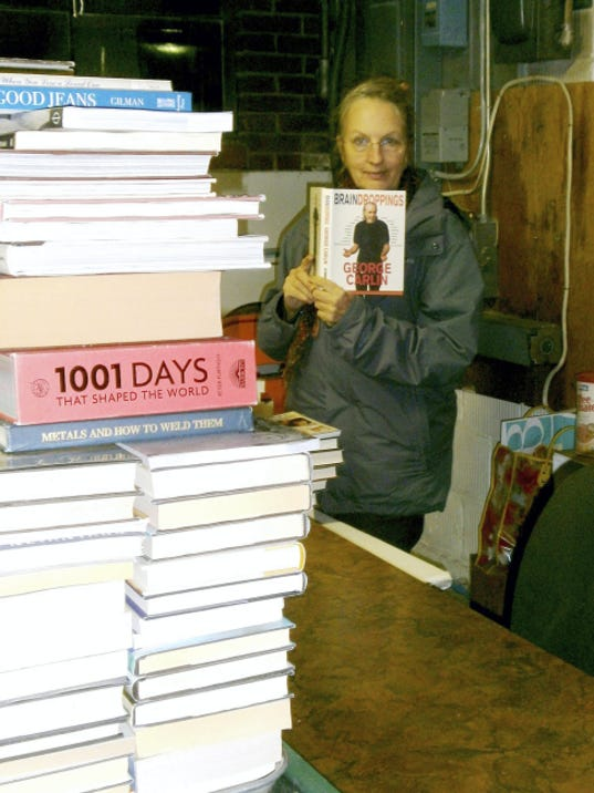 Friends of Legal Services volunteer Katy Clay stands by a pile of books that will be offered for sale at the 31st annual Friends of Legal Services Book Sale May 8 to 10 in Laird Hall, Wilson College, Chambersburg.