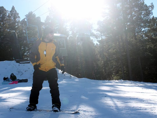 In this 2015 file photo, this visitor waits for others to clear the trail before heading down the mountain on his snowboard.
