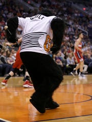 The Gorilla runs off the court with the drumstick.