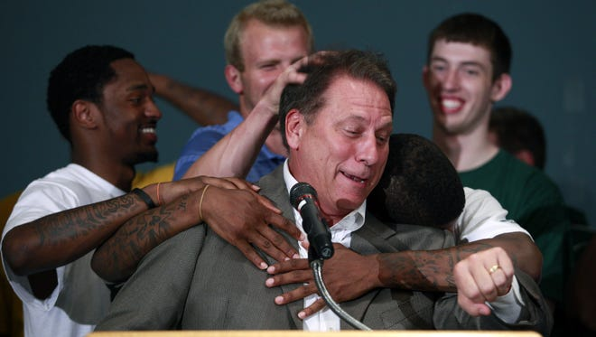 FILE - In this June 15, 2010, file photo, Michigan State basketball coach Tom Izzo, center, is hugged by players, including Kalin Lucas, left, Austin Thornton, center rear, Korie Lucious, right front, and Garrick Sherman, right rear, during a news conference in East Lansing, Mich., announcing that he will stay at Michigan State instead of moving to the NBA  to coach the Cleveland Cavaliers. Allen Iverson, Shaquille O'Neal, Tom Izzo, Sheryl Swoopes, Yao Ming and Jerry Reinsdorf have been inducted into the Basketball Hall of Fame. The announcement was made in Houston, Monday, April 4, 2016,  in advance of Monday night's national championship between Villanova and North Carolina. (AP Photo/Al Goldis, File)