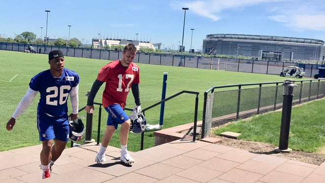 New York Giants rookies Saquon Barkley (26) and Kyle Lauletta (17) leave the practice field Monday morning after participating in the team's first OTA (organized team activity) of the spring in East Rutherford, NJ.
