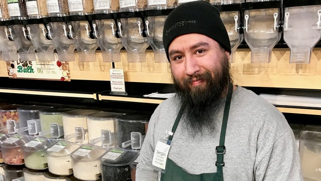 Sergio Barrios, assistant grocery manager at Good Harvest Market, shows off his favorite bulk food: dark chocolate banana chips.