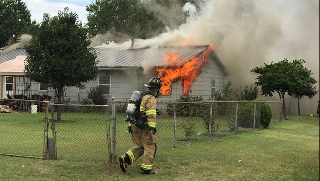 Flames shoot out of a back window of a home in the 100 block of Dundee Drive Tuesday afternoon on the southeast side of Wichita Falls. The fire was called in at about 2:30 p.m. Nine units from the Wichita Falls Fire Department responded to the fire, as well as two Wichita County Sheriff's Office deputies.