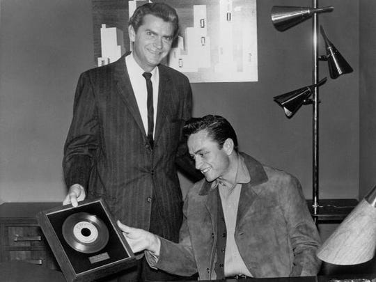 "MEMPHIS, TN - MAY 1:  Sun Records founder Sam Phillips poses for a portrait with country singer/songwriter Johnny Cash as he gives him a framed record of the song ""I Walk The Line"" to commemorate a milestone in album sales which was released on May 1, 1956 in Memphis, Tennessee. (Photo by Colin Escott/Michael Ochs Archives/Getty Images)"