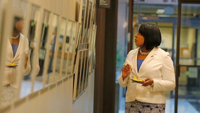 Rochester Mayor Lovely Warren looks over a row of images at the opening reception.
