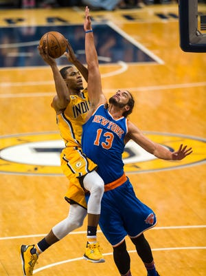 Pacers guard Glenn Robinson III, left, goes up to shoot as he is defended by Knicks center Joakim Noah (13) during Saturday's game in Indianapolis. (AP Photo/Doug McSchooler)