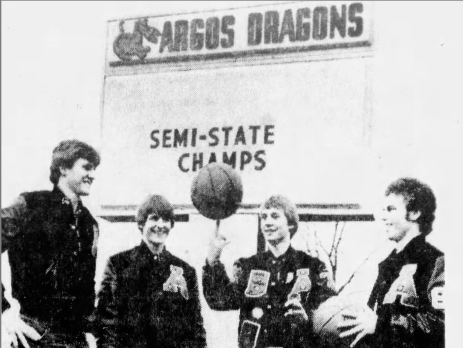 FILE – Bill O'Dell (far left), Don O'Dell and Dave Calhoun (far right) watch Mark Malone spin the ball on his finger outside Argos High School.