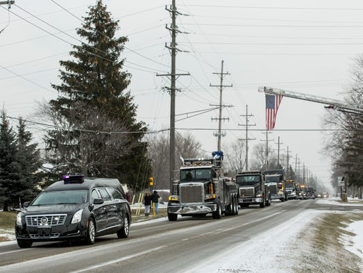 A hearse leads a line of hundreds of tow trucks and