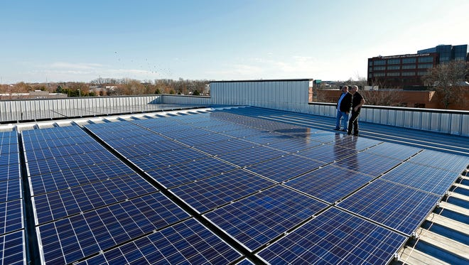 (from left) Christopher McNeese, A&B Cycle owner, and Patrick Winstead, A&B Cycle general manager, overlook the solar panels on the roof of A&B Cycle in south Springfield on Dec. 10, 2015.