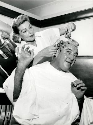 """Here's George Raymond Wagner, better known to wrestling fans as """"Gorgeous George."""" He's mentioned  in the quiz, but is he the answer? Here, he has his hair styled by Dorothy Rogers at Memphis' Claridge Beauty Shop."""