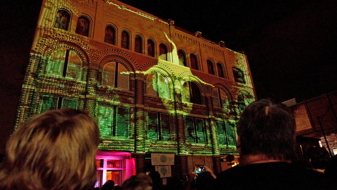 A crowd watches a projection during the LUMA 2015 festival on State Street in downtown Binghamton.