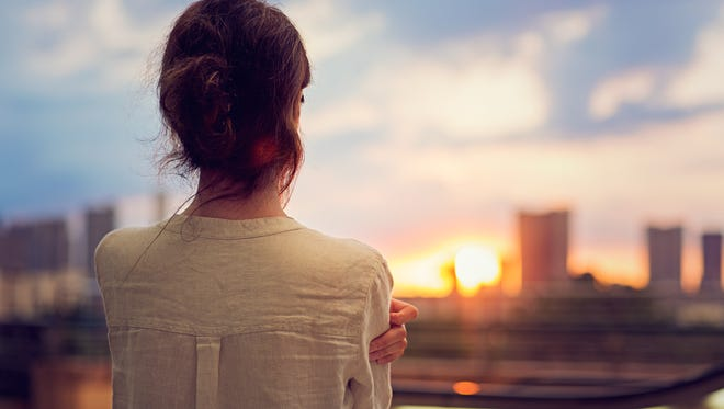 Young girl is watching sunset.