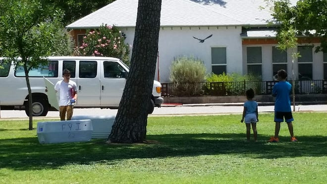 Two children wait for the free-lunch distribution at Pioneer Women's Park, 500 W. Las Cruces Ave., on Thursday. The free breakfast-and-lunch program for children in the Las Cruces area had some hiccups in its first week, including a day in which some sites were skipped and late deliveries at other sites.