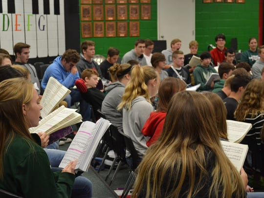 Students practice a section of Handel's Messiah in the choir room.