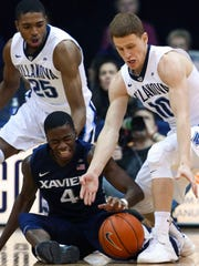 Salesianum product Donte DiVincenzo (right) grabs a steal from Xavier's Edmond Sumner in front of teammate Mikal Bridges in the first half at Villanova Tuesday.