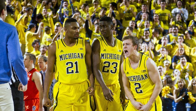 Spike Albrecht (2) celebrates with teammates Zak Irvin (21) and Caris LeVert during happier times.