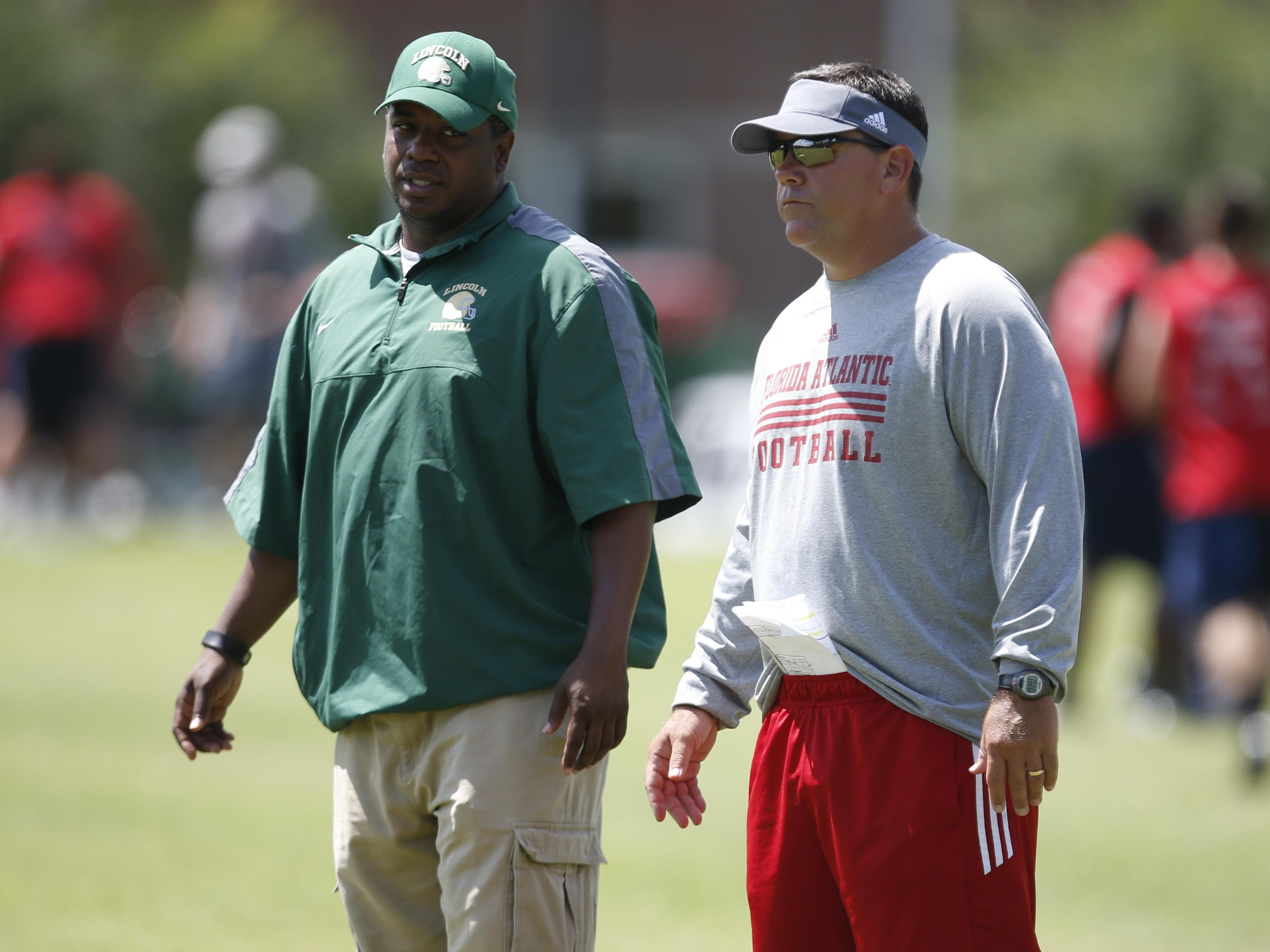 Lincoln High School Coach Yusuf Shakir, left, talks to Florida Atlantic head coach Charlie Partridge during drills at the Florida Atlantic Football Camp at Lawson Chiles High School on Friday.