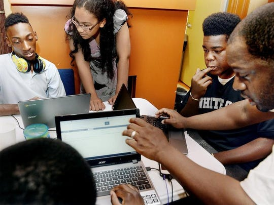 Montana Howard, left, 16, program manager Debralyn Woodberry-Shaw, Evan Nevels, 15, and mentor Jomari Peterson work on building websites for their products.
