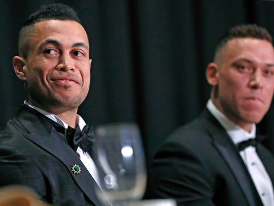National League Most Valuable Player Giancarlo Stanton, left, and American League Rookie of the Year Aaron Judge sit at the dais listening to speakers during the New York Chapter of the Baseball Writers' Association of America annual dinner in New York, Sunday, Jan. 28, 2018, where both picked up their awards. (AP Photo/Kathy Willens)