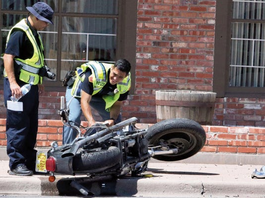 El Paso police traffic investigators look over a motorcycle involved in a traffic accident at Montana Avenue near Huckleberry Street on Wednesday in Central El Paso. Two riders on the motorcycle were transported to a hospital.