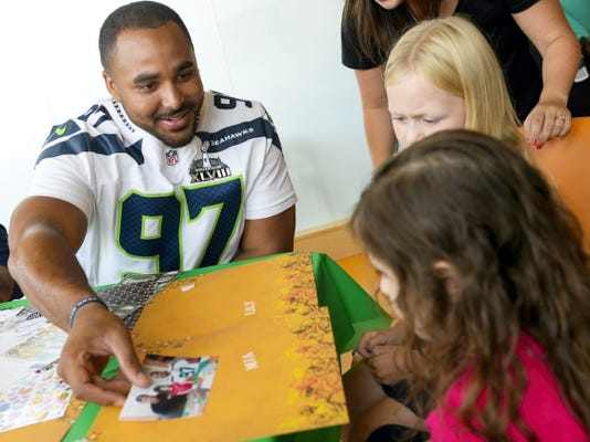 Jordan Hill works on a scrap book page with two children Tuesday at the Penn State Hershey Children's Hospital.