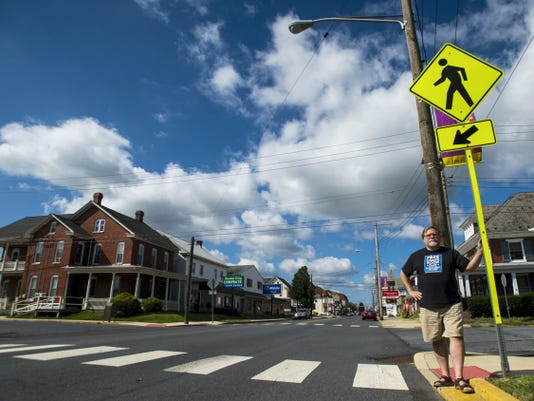 Ralph Watts, owner of Comic Books and Paperbacks Plus at 201 E. Main St., Palmyra, stands by the crosswalk in front of his store last week. The Palmyra councilman has a plan to raise money to purchase more crosswalks signs for the borough.