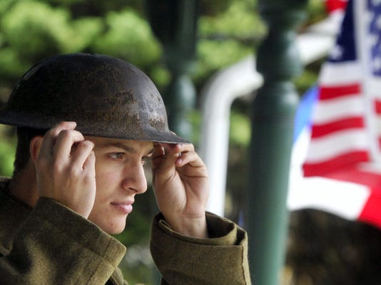 Tristan Holley, of Harrisburg, puts on his helmet while portraying a U.S. infantry soldier from World War I. The event at Muddy Creek Forks continues on Sunday from 1 to 5 p.m. It's free and open to the public.