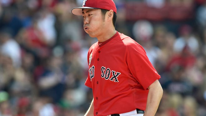 Boston Red Sox relief pitcher Koji Uehara reacts walking off the mound during the ninth inning in game one at Fenway Park.