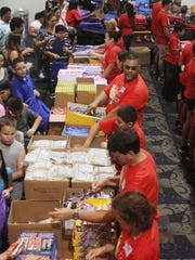 Volunteers work to hand out school supplies at Harborside Event Center during last year's Big Backpack Event in Fort Myers. This year, the event is set for July 31.