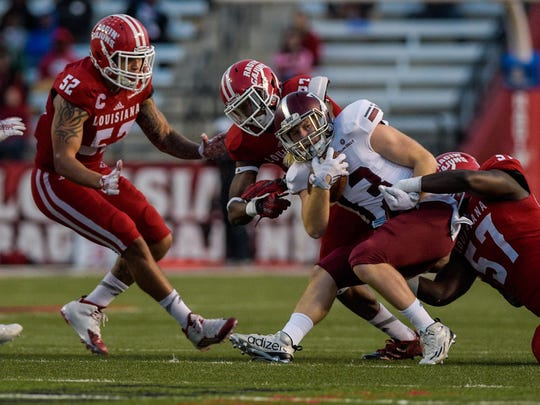 Troy Trojans wide receiver K.D. Edenfield (13)  is tackled by a host of UL Ragin' Cajuns defensive players during the first half of an NCAA football game at Cajun Field in Lafayette, La., Saturday, Dec. 5, 2015.