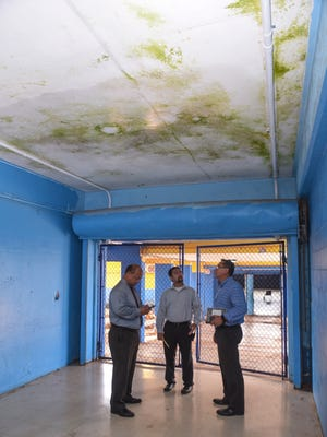 Principal Patrick Egrubay, center, looks up at algae and mold growing at a moist section of ceiling in a hallway at V.S.A. Benavente Middle School on Tuesday, June 6, 2017. Guam Department of Education Superintendent Jon Fernandez took a tour of the school to determine what repairs or improvements would need to be addressed before the start of the next school year. From left: Fernandez, Egrubay and Christopher Anderson, GDOE student support services administrator.