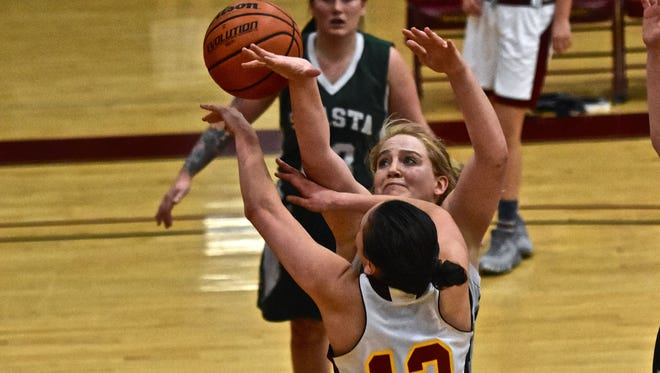 Shasta College's Rachel Eubanks fights for a loose ball against College of the Redwoods' Anna Nelson Wednesday night in Eureka. Shasta won 66-61 in overtime.