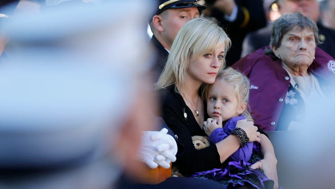 Kimberly Chiapperini holds her daughter Kylie during a ceremony at the New York State Fallen Firefighters Memorial in Albany.