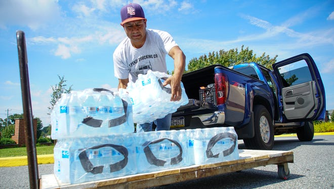 Guadalupe Aguilar, of Kennett Square, Pa., loads packs of bottled water on to a cart to take into St. Elizabeth Ann Seton Church in Bear, where donated items for Hurricane Harvey victims were being collected on Thursday.