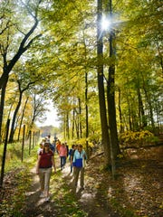 A group walks along the Old St. Joe Road Trail at St. John's Abbey Arboretum in 2015.