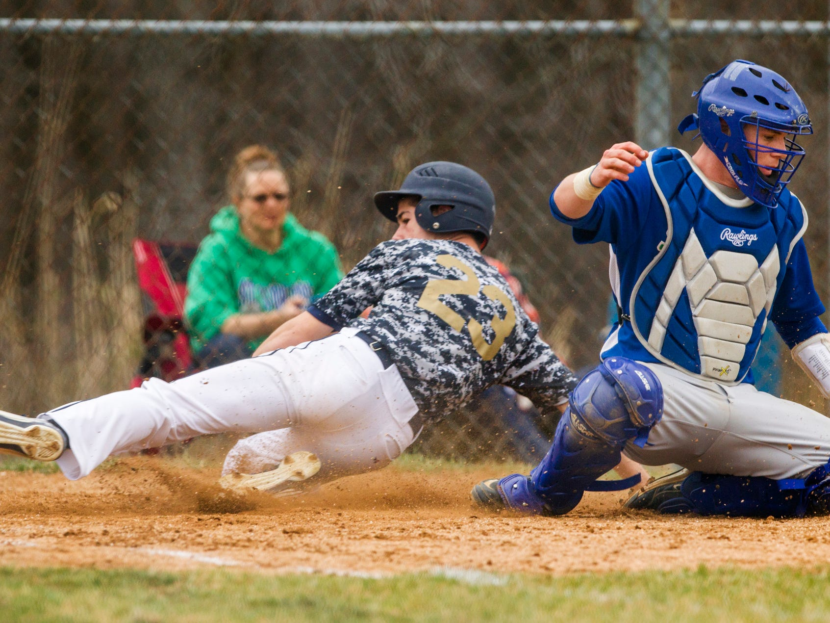 Delaware Military Academy's Shane Carney slides in safe at home plate to score DMA's first run of their a game against St. Georges at Newark National field on Tuesday afternoon.