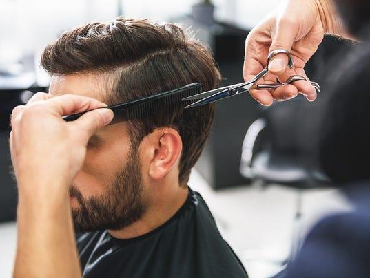 Barber using scissors and comb