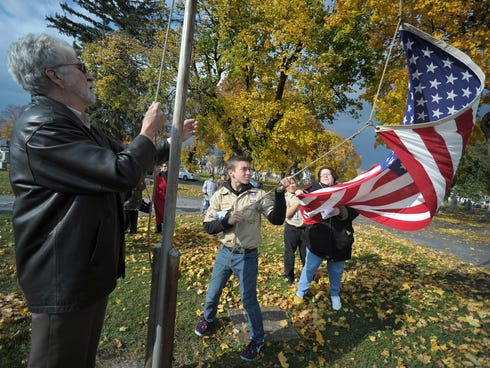 Dave Gilbert, left, of Easton, and Boy Scout Troop #6 member Hunter McGary, right, 14, of Easton, raise an American Flag during a Veterans Day program on Nov. 10, 2013.