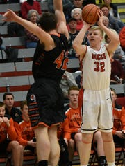 Yankton's Matthew Mors spots up for a three-pointer as Washington's Isaac Goeman flies in on defense during their boys' basketball game on Tuesday at the YHS Gym.