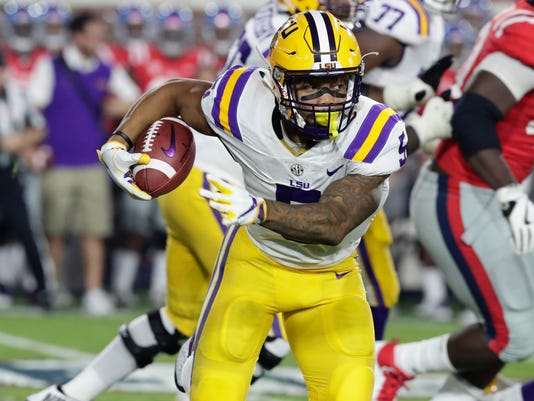 This Oct. 21, 2017 photo shows LSU running back Derrius Guice (5) running through Mississippi defenders in the first half of an NCAA college football game in Oxford, Miss. Running backs will take center stage as No. 14 Notre Dame faces No. 16 LSU in the Citrus Bowl. The Irish's Josh Adams is 13th nationally in rushing while the Tigers' Derrius Guice has posted his second straight 1,000-yard season. (AP Photo/Rogelio V. Solis)