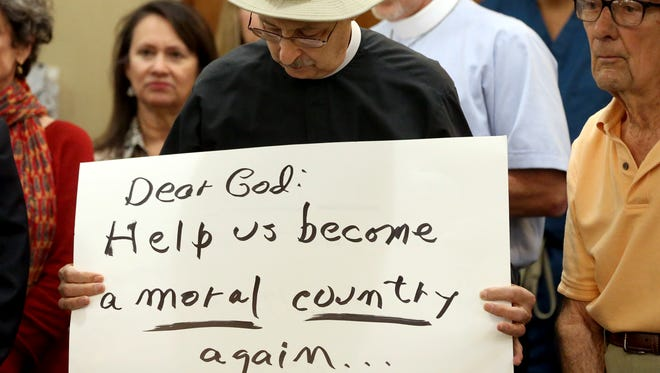 Father Bruce Wilson holds a sign during a news conference on the Immigration executive orders signed by Donald Trump on Monday, Jan. 30, 2017, at the office of Congressman Blake Farenthold in Corpus Christi.