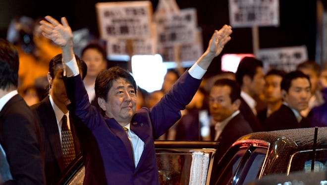 Japan's Prime Minister and ruling Liberal Democratic Party leader Shinzo Abe waves to his supporters while leaving his last campaign stop in Tokyo, on Oct. 21, 2017.